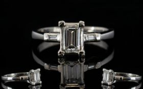 Platinum Emerald Cut Diamond Ring The central stone, set between two emerald cut diamond shoulders,