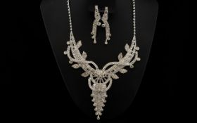 White Crystal Necklace and Drop Earrings Set, a design with layers of trails, leaves, loops,