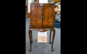 An Early 20th Century Mahogany Queen Anne Style Serpentine Fronted Chest Two hinged doors