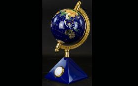 Small Decorative Globe and Clock. Attractive globe in deep blue and gold, on pyramid base containing
