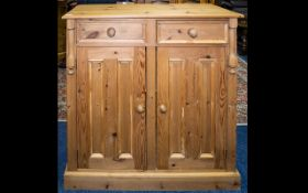 A Freestanding Pine Cabinet with panelled pine doors, two drawers on a plinth base,