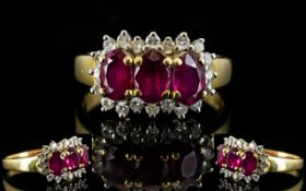 18ct Gold Ruby And Diamond Cluster Ring With three central oval cut rubies,