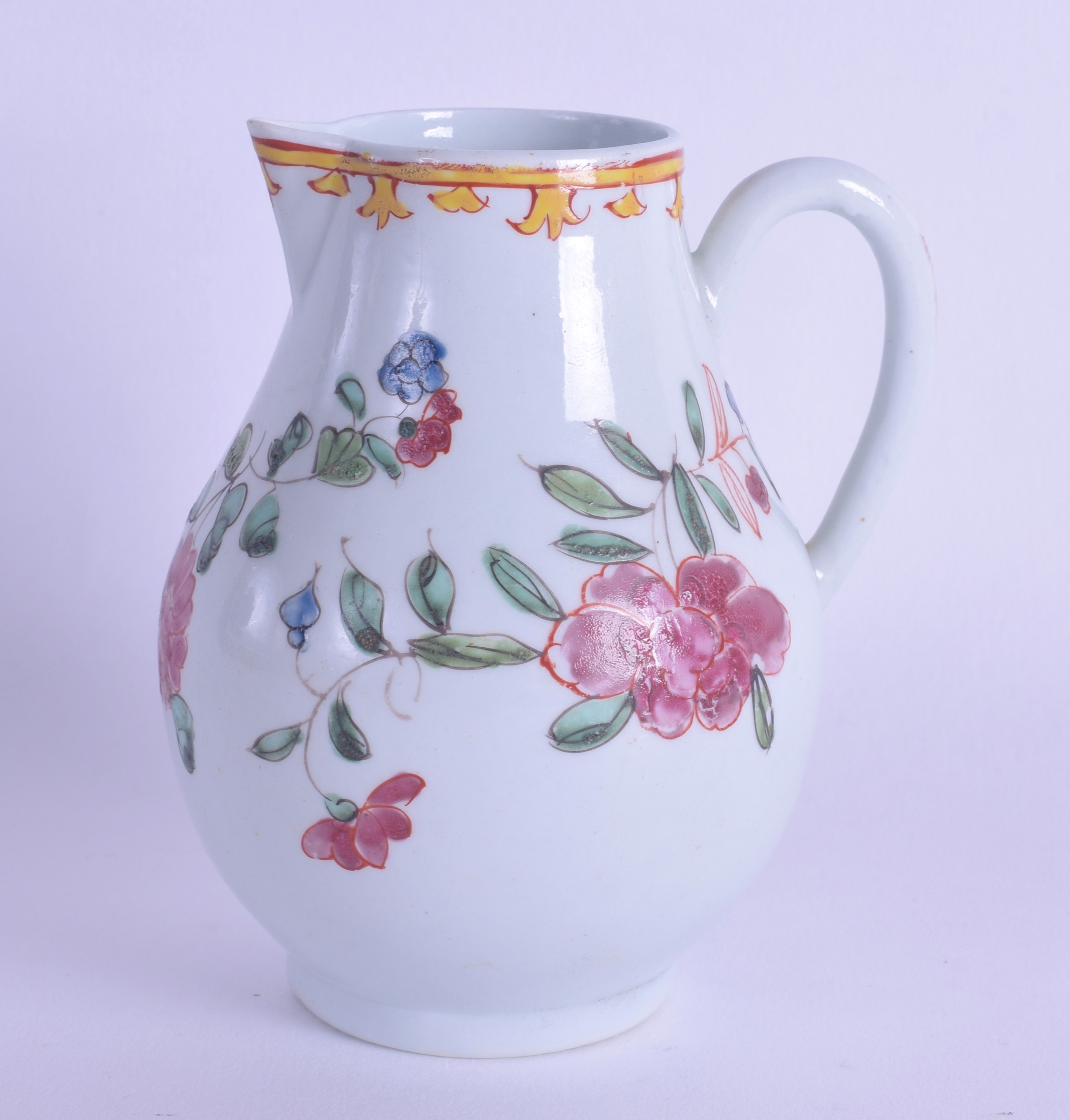 Lot 120 - An 18th c. Liverpool sparrow beak jug painted in famille rose style under a bright yellow border.