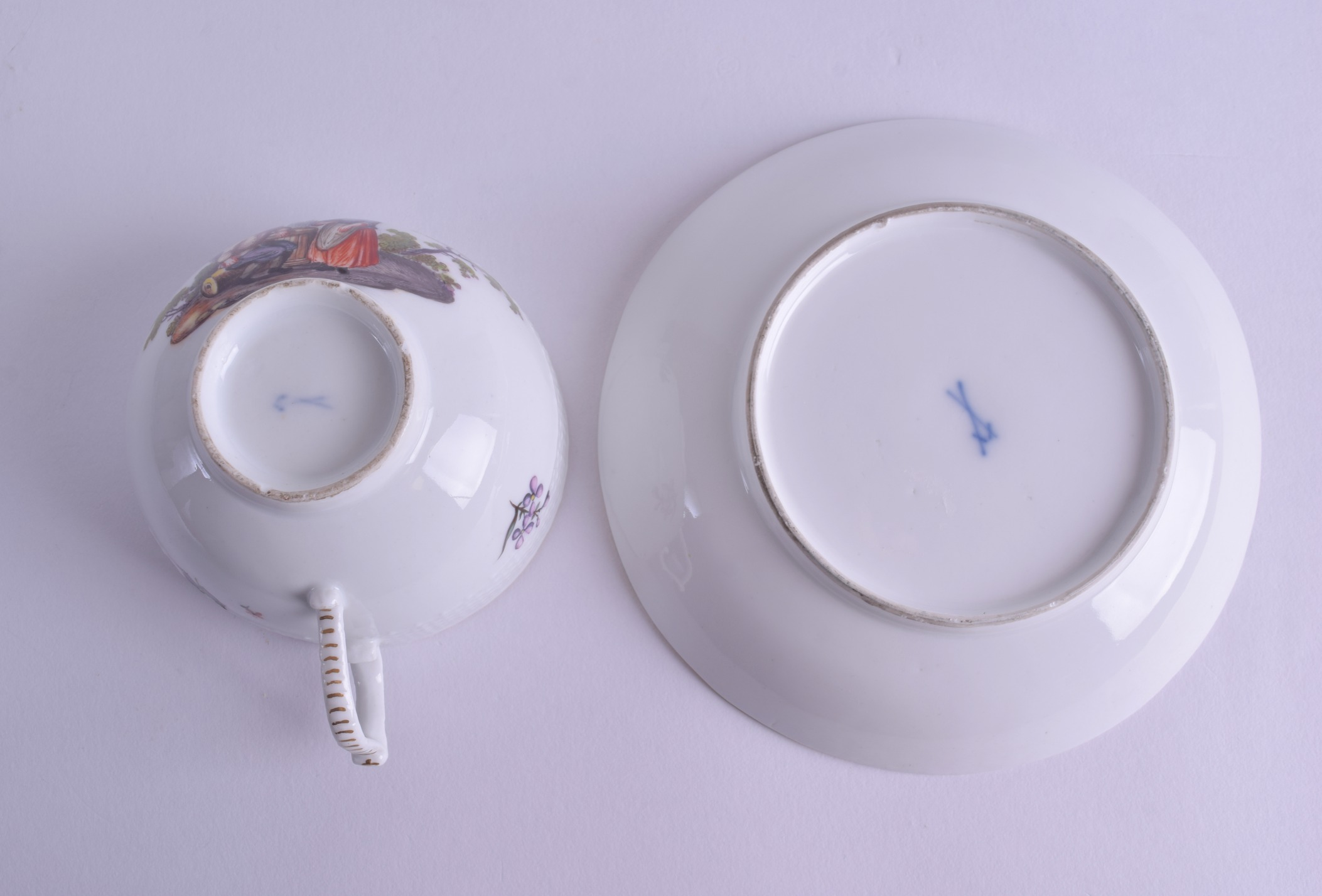 Lot 109 - AN 18TH/19TH CENTURY MEISSEN PORCELAIN TEACUP AND SAUCER painted with figures within landscapes.