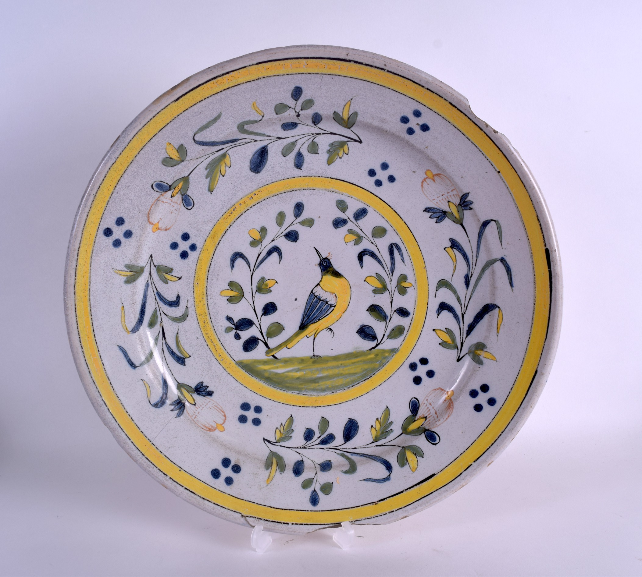 Lot 75 - AN 18TH CENTURY CONTINENTAL FAIENCE TIN GLAZED DISH painted with a bird roaming amongst foliage.