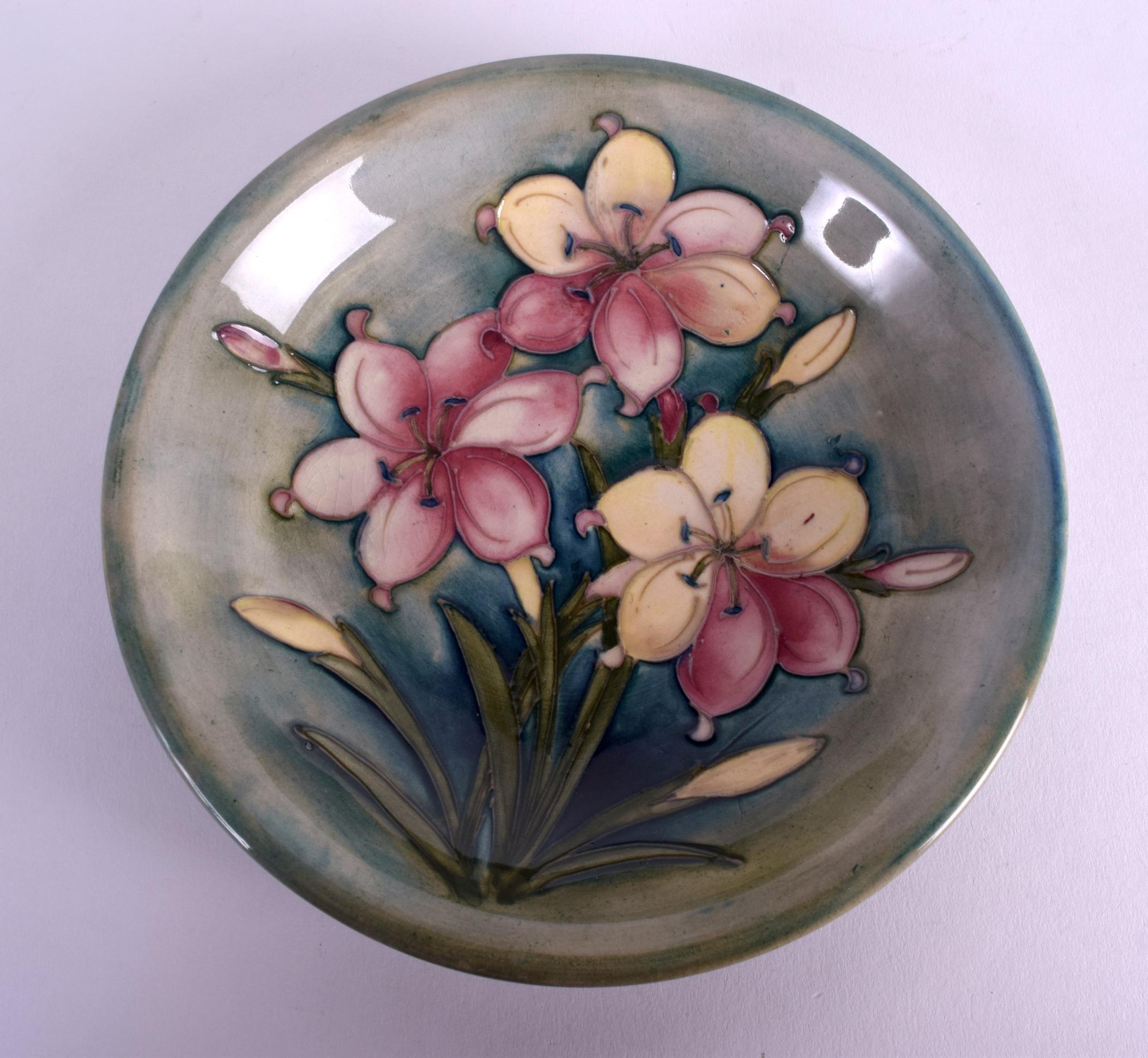 Lot 89 - A WILLIAM MOORCROFT CIRCULAR DISH decorated with three floral sprays. 18 cm diameter.