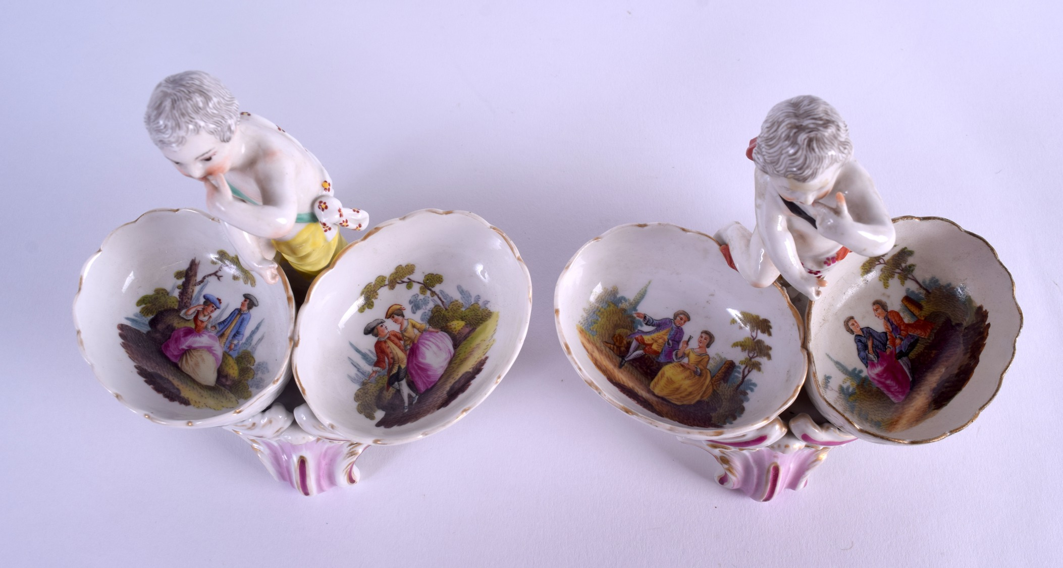 Lot 55 - A PAIR OF 19TH CENTURY KPM BERLIN PORCELAIN FIGURAL TABLE SALTS painted with figures within