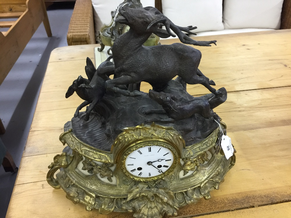 Lot 28 - Clocks: Table clock in gilt metal and spelter, mounted with a stag hunt scene. the movement, Japy