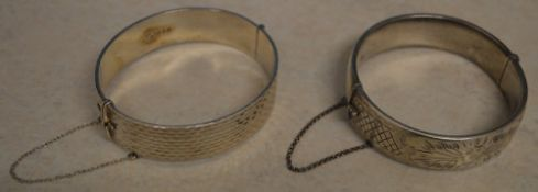 2 decorated silver bangles, both with safety chains, total approx weight 2.
