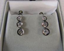 Pair of platinum triple graduated diamond earrings (total carat weight 0.