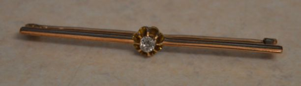 9ct gold bar brooch set with a single central diamond in an open claw setting,