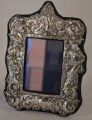 Ornate Britannia silver photo frame surrounded by repousse characters including a cavalier and