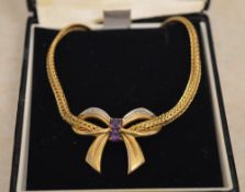 9ct gold necklace with a diamond and amethyst pendant shaped as an ornate bow,