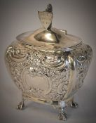 An ornate Edwardian silver tea caddy decorated with flowers and leaves,