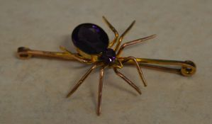 9ct gold bar brooch in the form of a spider set with two amethyst style stones to the body,