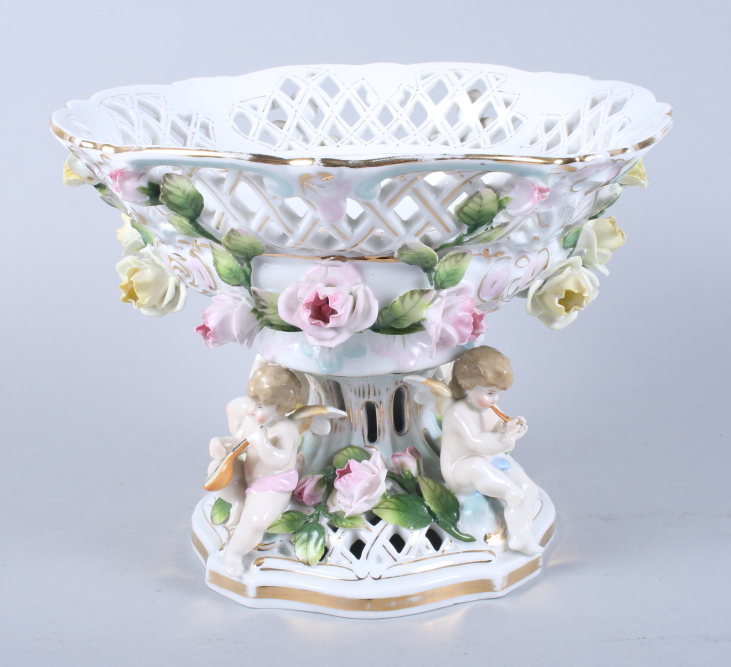 """Lot 9 - A Continental porcelain table centre with cherub and flower decoration, 10"""" dia (small chips)"""