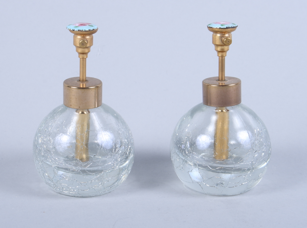 Lot 48 - A pair of early 20th century ice glass scent bottles, each atomiser with guilloche enamel of a