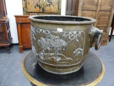 AN ORIENTAL BRONZE JARDINIERE WITH PANELS OF FIGURAL DECORATION AND TWIN LOOSE RING HANDLES. H.