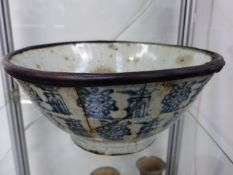 A LARGE ORIENTAL BLUE AND WHITE POTTERY BOWL WITH BAMBOO RE-ENFORCED RIM. 26CM DIAMETER