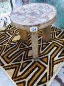AN AFRICAN CARVED DISH TOP STOOL WITH BEAD DECORATION AND A SMALL TEXTILE PANEL.