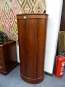 AN INTERESTING SCANDINAVIAN DANISH SANTOS ROSEWOOD OVAL FORM PEDESTAL CABINET WITH SINGLE DOOR.