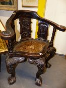 A COLONIAL CARVED HARDWOOD CANE SEAT TUB FORM ARMCHAIR IN THE CHIPPENDALE MANNER WITH SCROLLING