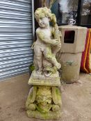 A VINTAGE CARVED STONE FOUNTAIN AND SURROUND SURMOUNTED WITH A FIGURE OF A CHERUB.
