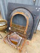 A VICTORIAN CAST IRON FIRE SURROUND AND A CAST IRON LOG BASKET.