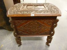 AN ORIENTAL CARVED HARDWOOD LIFT TOP BOX RAISED ON SERPENT FORM LEGS, THE TOP CARVED WITH WALLED
