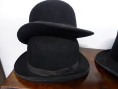 A SELECTION OF VINTAGE HATS COMPRISING FOUR BOWLERS AND A TOP HAT.