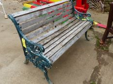 AN ANTIQUE CAST IRON AND TEAK GARDEN BENCH LATER PAINTED GREEN.