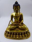A GILT BRONZE TIBETAN FIGURE OF BUDDHA SEATED ON LOTUS BASE. H.27.5cms.