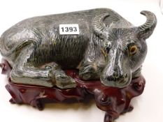 A CHINESE GREEN GLAZED FIGURE OF A RECUMBENT WATER BUFFALO ON CONFORMING CARVED HARDWOOD STAND. W.