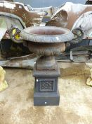 AN ANTIQUE CAST IRON TWO HANDLED GARDEN URN ON SQUARE PLINTH BASE.