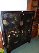 A CHINESE BLACK LACQUER TWO DOOR CABINET WITH POLYCHROME LANDSCAPE DECORATION. H.137 x W.107cms.