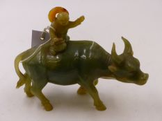 A CHINESE CARVED JADE FIGURAL GROUP OF A BOY RIDING A WATER BUFFALO. H.14.5cms.