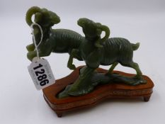 A CHINESE GREEN JADEITE MODEL OF TWO RAMS CAVORTING WITH PLINTH. L.14cms. (boxed)