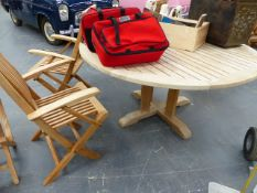 A GOOD QUALITY TEAK CIRCULAR PATIO TABLE AND A MATCHING SET OF SIX FOLDING ARMCHAIRS.