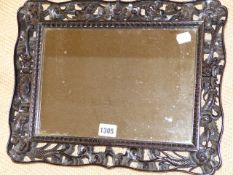 A CHINESE CARVED HARDWOOD FRAME WITH PIERCED DRAGON DECORATION AND INSET MIRROR PLATE. H.32 x W.