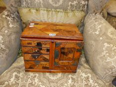 A JAPANESE PARQUETRY INLAID SMALL CABINET WITH NUMEROUS FITTED DRAWERS, ENGRAVED BRASS MOUNTS AND