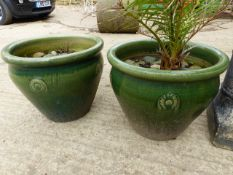 A PAIR OF GLAZED LARGE GARDEN PLANTERS AND A DEMI LUNE GARDEN SEAT.