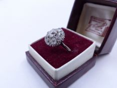 AN OLD CUT DIAMOND CLUSTER RING IN A WHITE METAL SETTING (TESTED AS WHITE GOLD). THE CENTRAL DIAMOND