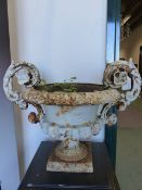 A PAIR OF ANTIQUE CAST IRON TWO HANDLE GARDEN URNS. W.51 x H.40cms.