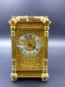 A VICTORIAN CASED CARRIAGE CLOCK WITH FLORAL CHASED DECORATIVE DIAL AND ENAMEL CHAPTER RING.