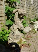 AN OLD WEATHERED COMPOSITE STONE GARDEN FIGURE OF A PUTTI WITH FISH.