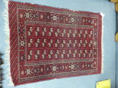 A PERSIAN BOKHARA RUG. 126 x 95cms TOGETHER WITH A SMALLER BELOUCH RUG. (2)