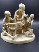 A JAPANESE CARVED IVORY GROUP OF TRADESMEN AND CHILDREN ON A SHAPED BASE WITH INSET SIGNATURE