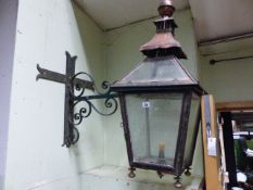 AN ANTIQUE COPPER OUTSIDE LANTERN ON WROUGHT IRON WALL BRACKET. H.90cms.