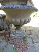 A CLASSICAL STYLE GARDEN URN RAISED ON TALL SQUARE PLINTH.
