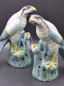 A PAIR OF CHINESE POLYCHROME DECORATED FIGURES OF HAWKS, EACH PERCHED ON A ROCKY OUTCROPPING. H.